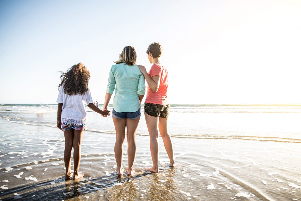 Lesbian mothers with daughter by the beach