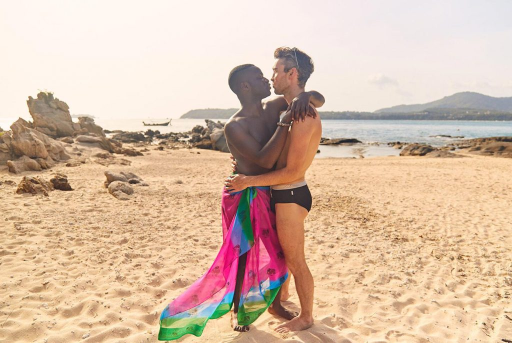 A gay couple kiss on a beach in Thailand
