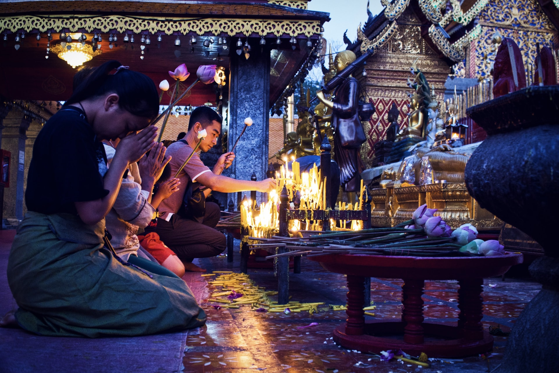 People paying their respects at a Buddhist temple in Chiang Mai, Thailand