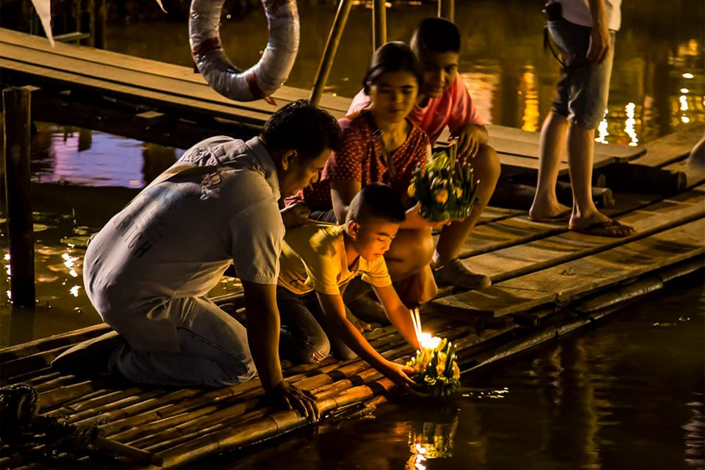 A Thai family release krathongs into a stream for Loy Krathong festival, Thailand.