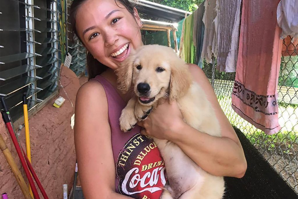 A happy volunteer is pictured with a dog at Baan Unrak Thai Animal Sanctuary in Sangkhlaburi, Thailand