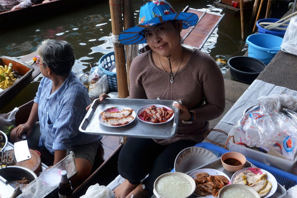 A friendly food vendor smiles for the camera at a floating market in Thailand