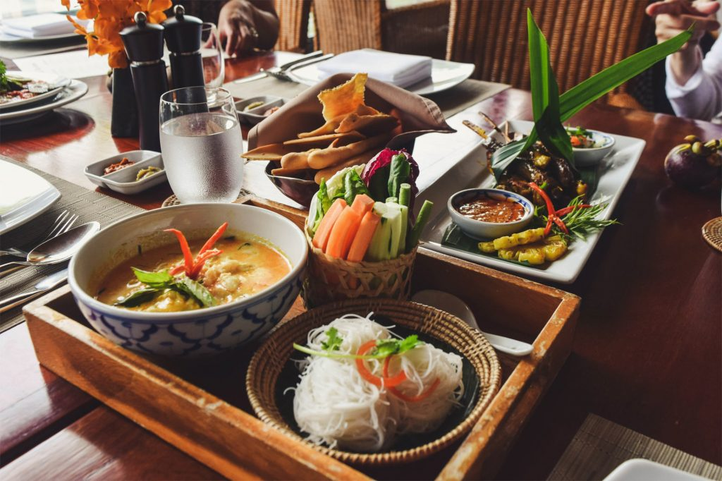 A Thai meal consisting of several plates of colourful, fresh foods