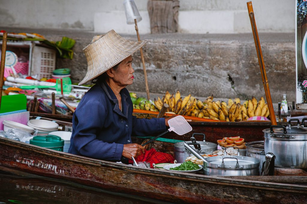 A trader in a boat at a floating market in Thailand