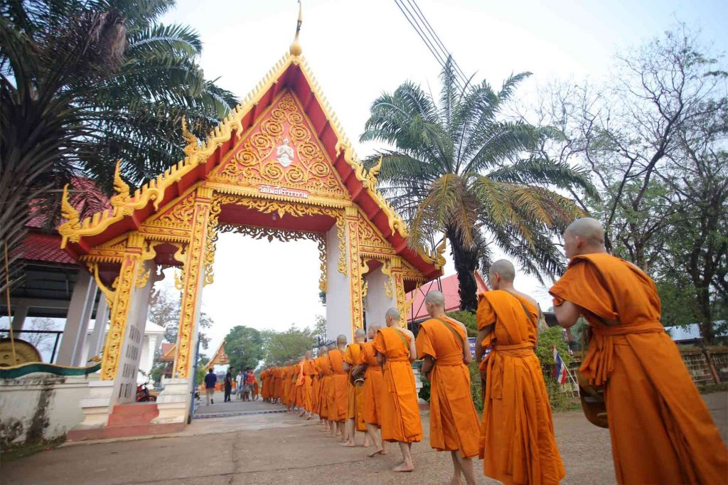 Buddhist monks queuing outside a temple in Thailand