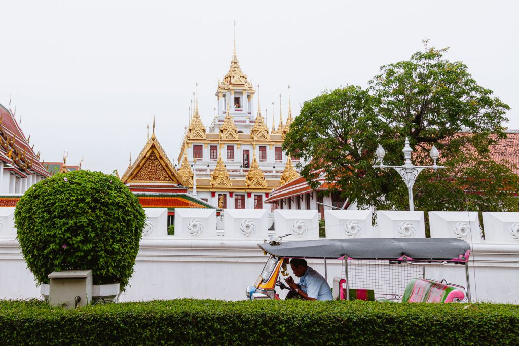 A tuk tuk is parked outside a temple in Bangkok, Thailand